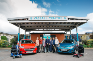 The first picture shows the front entrance of The Vassall Centre with two cars, two mobility scooters and seven members of Driving and Mobility Centre staff standing in front of them.