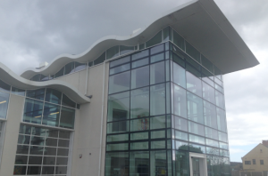 This picture shows the Safewise Centre in Weymouth, a modern multi storey building with a glass front and a wavy roof.