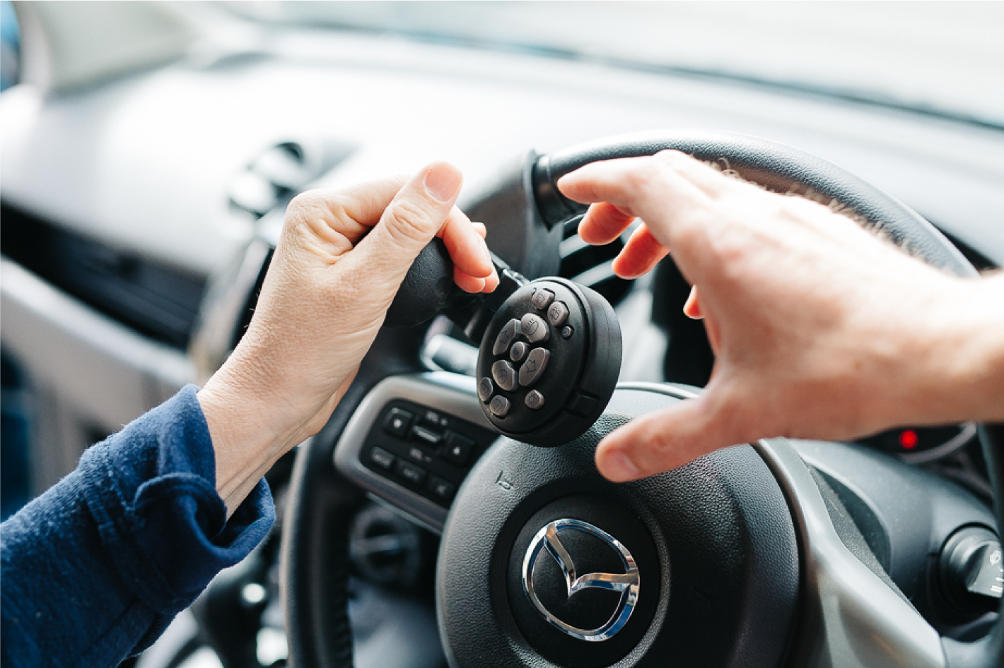 This picture shows a Lodgesons combined steering aid, remote secondary control unit, on a steering wheel, being used by a person using their left hand. Another person's hand is reaching in to assist that person.