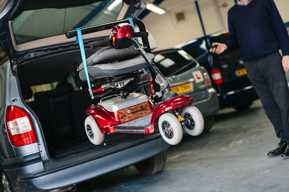 This picture shows a male driving advisor holding the control button of a Brigayd telescopic mobility scooter hoist, as the Monaco three-wheeled scooter is in mid-air before being loaded into the boot of a hatchback car with an open boot.