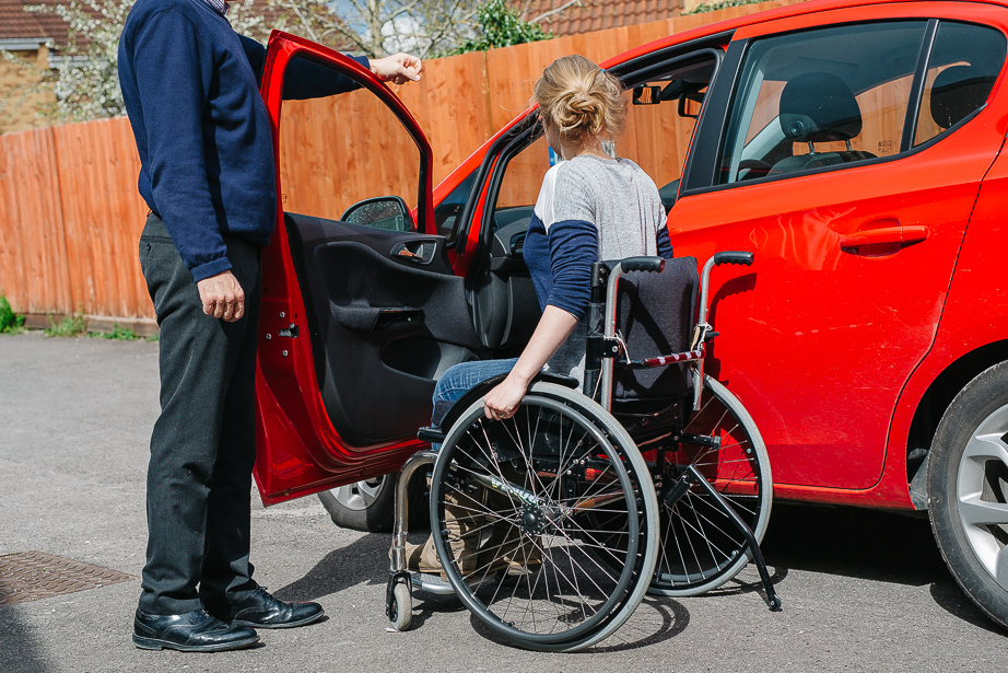 This picture shows a younger woman in a manual wheelchair approaching the open passenger door of a red car which is being held open by a male driving advisor.