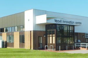 This picture shows the front entrance of Yeovil Innovation Centre, a two-storey modern building, on a completely sunny day.